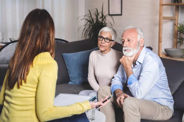 Senior couple resolves problems with an advisor stock photo