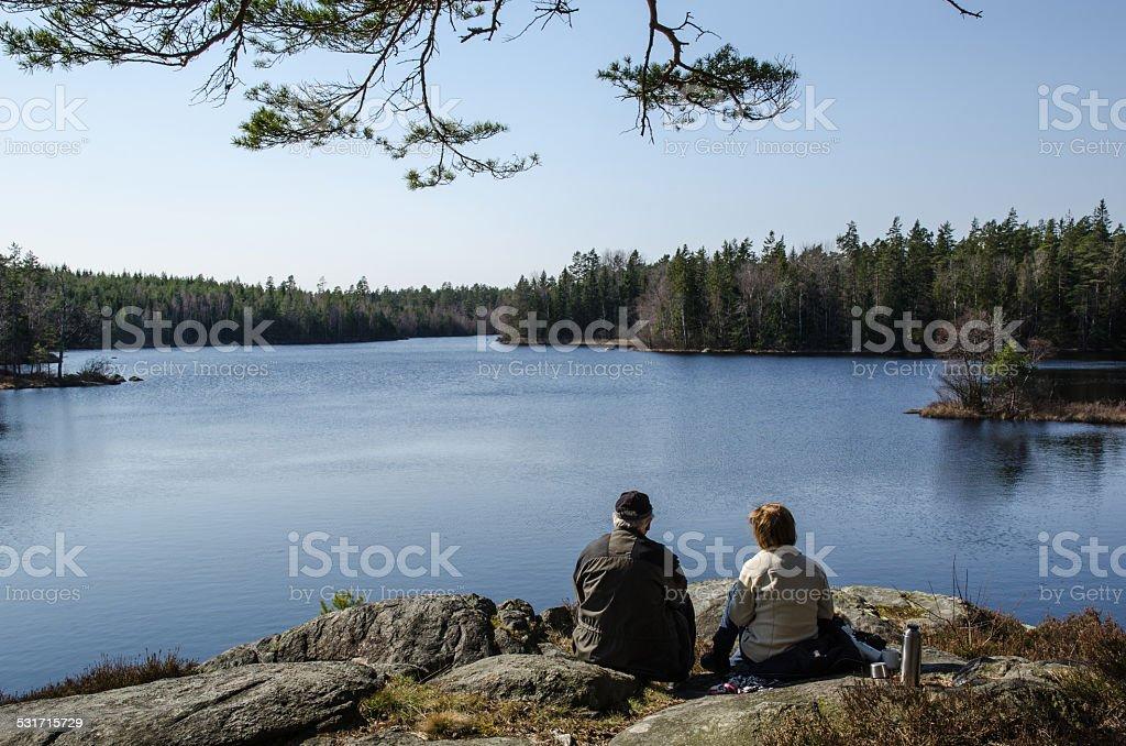 Senior couple resting at lake side stock photo