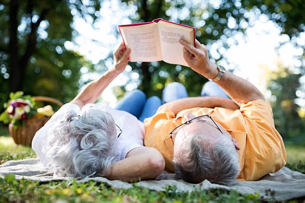 senior couple resting at park, reading a book - romantisches picknick stock-fotos und bilder