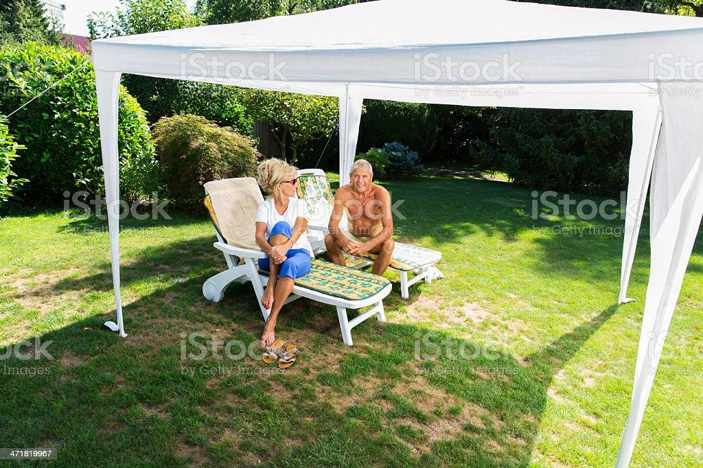 Senior couple resting in shade of garden tent stock photo
