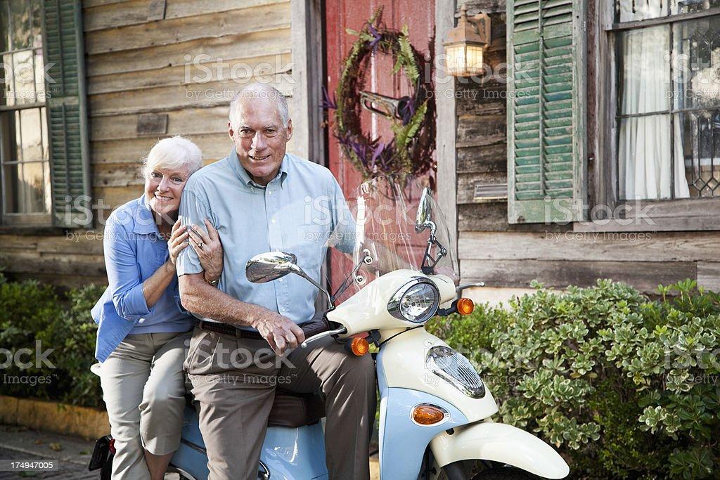 Senior couple riding motor scooter royalty-free stock photo