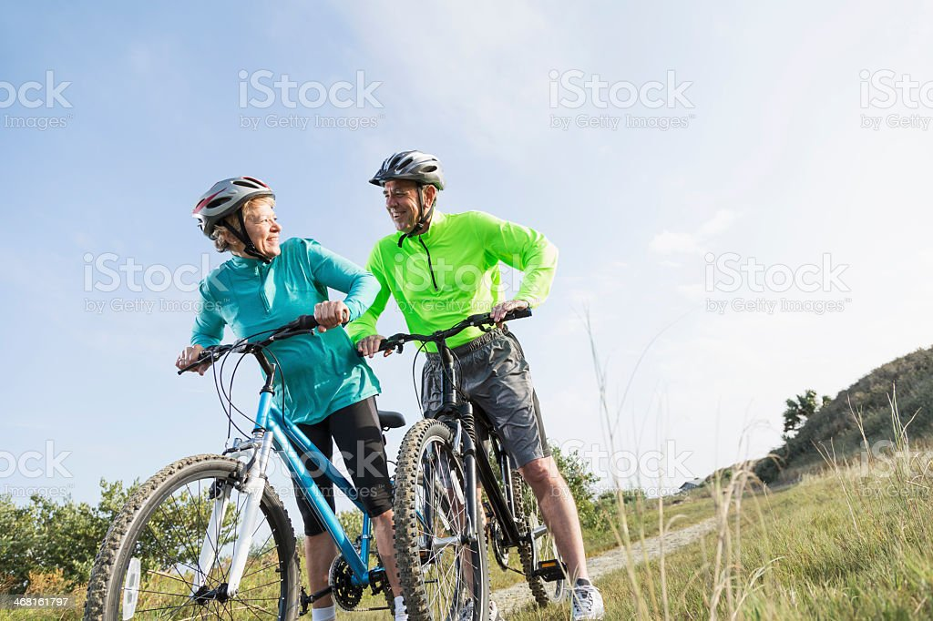 Senior couple riding mountain bikes stock photo