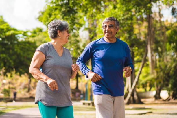 äldre par kör på park - senior walking bildbanksfoton och bilder