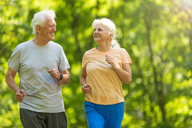 Senior couple running in park stock photo