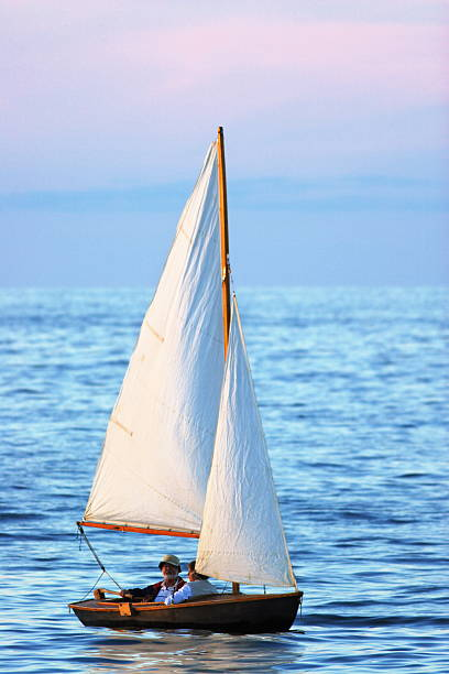 Senior Couple Sailing Sloop Sunset  sailing dinghy stock pictures, royalty-free photos & images