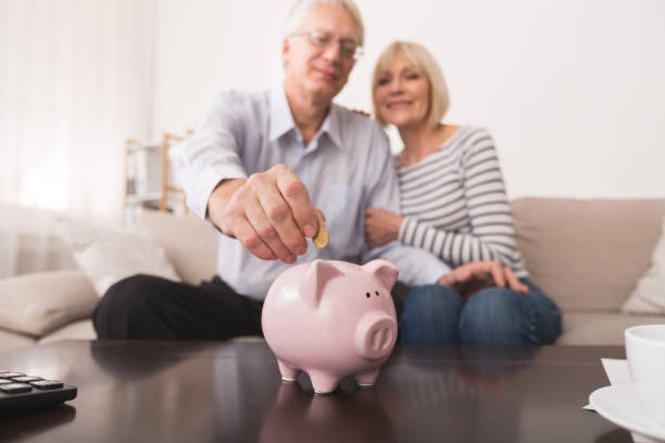 Senior couple saving money in piggybank at home Senior couple putting coin in piggybank, saving money at home pension stock pictures, royalty-free photos & images