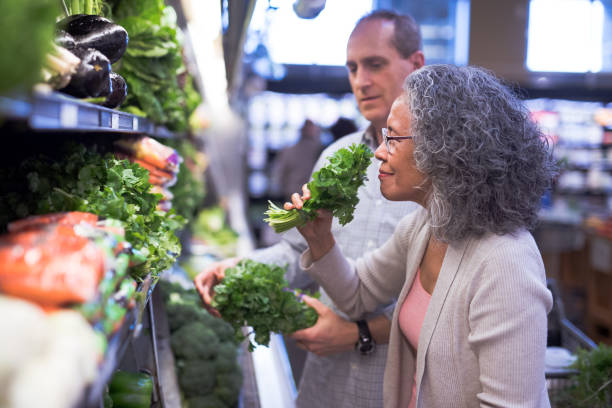 Senior couple selecting fresh herbs at the grocery store stock photo