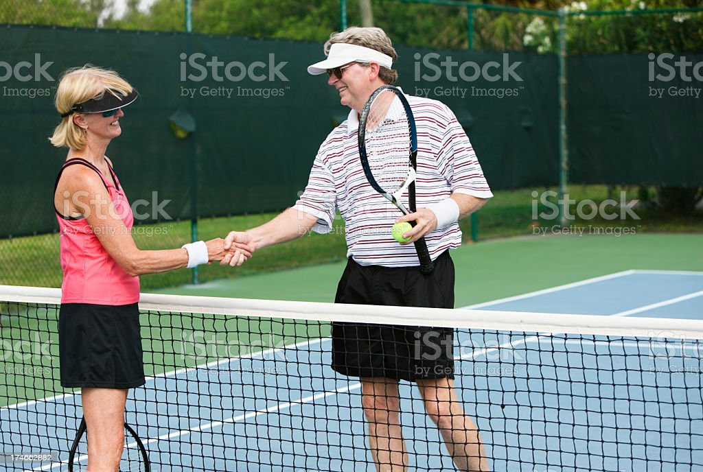 senior couple shaking hands after tennis match royalty-free stock photo