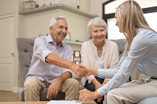 istock Senior couple shaking hands with financial advisor 1029343906