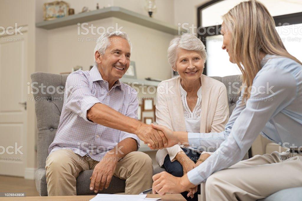 Couple de personnes âgées se serrant la main avec le conseiller financier - Photo