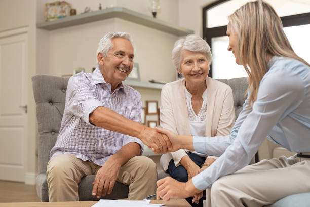 senior couple shaking hands with financial advisor - financial advisor with clients stock photos and pictures