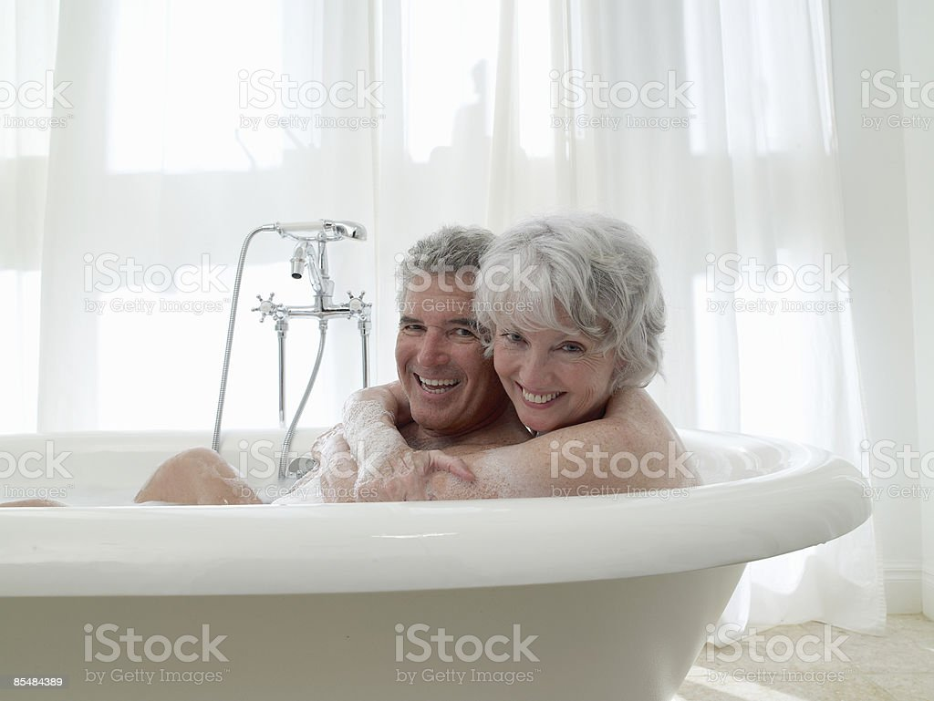 Senior couple share bath together laughing royalty-free stock photo