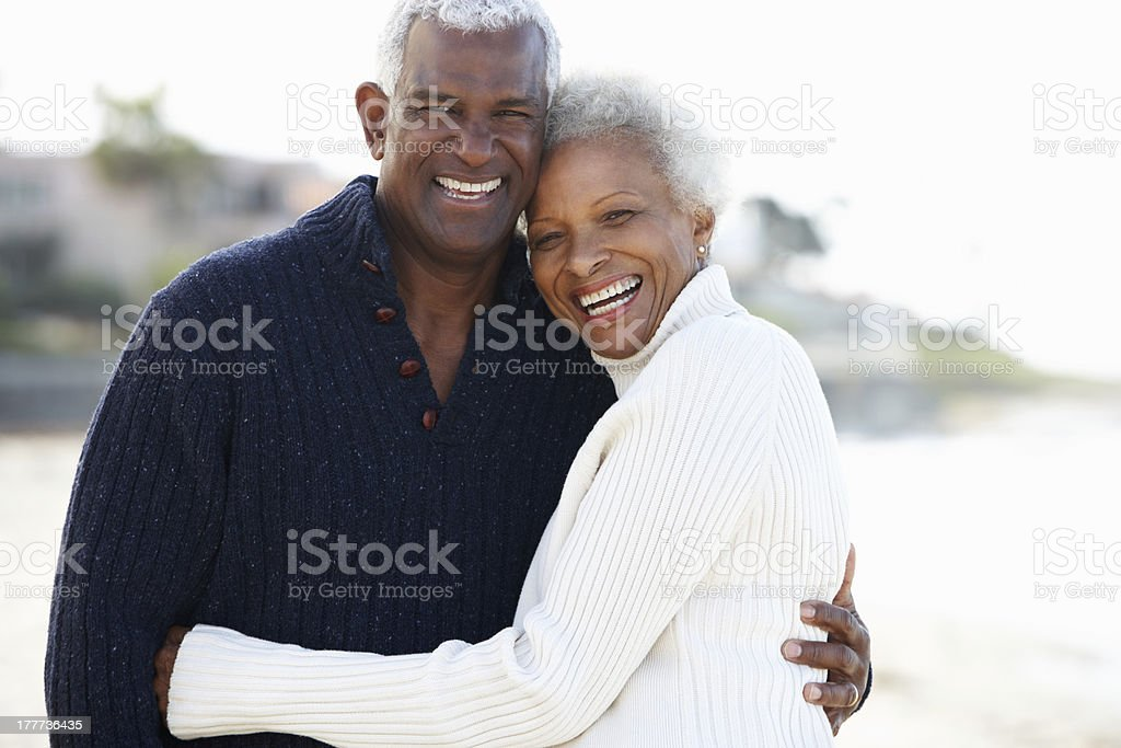 Senior couple sharing a romantic hug on the beach stock photo