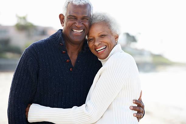 Senior couple sharing a romantic hug on the beach stock photo