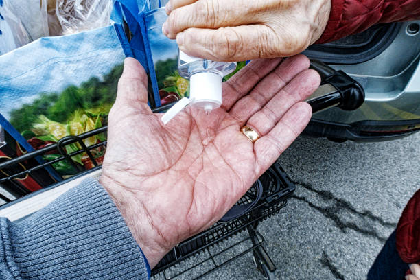 Senior Couple Sharing Hand Sanitizer After Supermarket Grocery Shopping A senior married couple sharing hand sanitizer before loading their car after grocery shopping at a retail supermarket. She is squirting a blob of alcohol-based liquid disinfectant hand sanitizer onto his outstretched palm from the small squeeze bottle she carries in her purse. Another