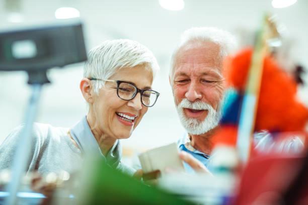 Älteres Paar für ein kleines weißes Leder Portemonnaie zusammen in einem Taschen und Accessoires Shop einkaufen – Foto