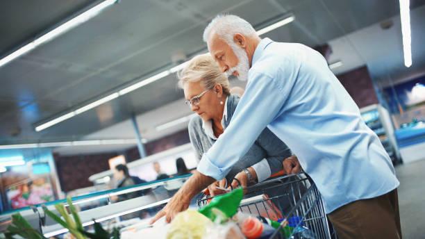 älteres paar einkauf im supermarkt. - kühlraum stock-fotos und bilder