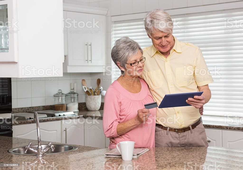 Senior couple shopping online with tablet pc stock photo