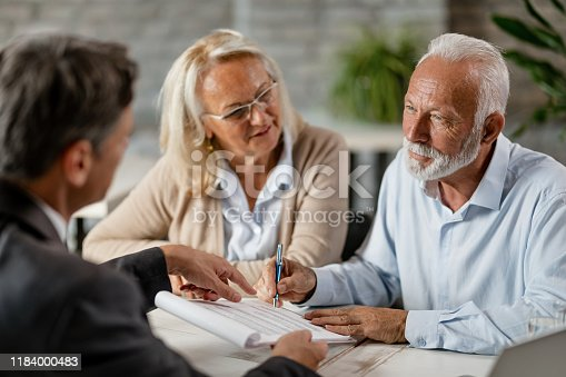 Mature couple having a meeting with bank manager and signing lease agreement in the office. Focus is mature man.