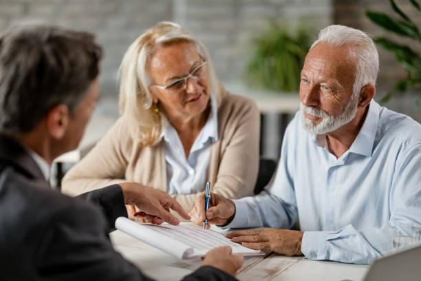 senior paar unterzeichnung einen vertrag, während ein treffen mit versicherungsvertreter im büro. - lifestyle stock-fotos und bilder