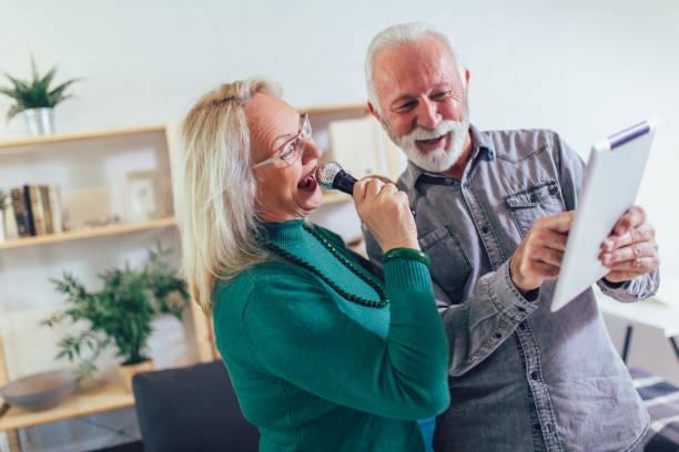 Senior couple singing karaoke at home, having fun. stock photo