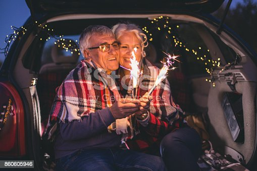 istock Senior couple sit in open car trunk and hold spark sticks in their hands 860605946