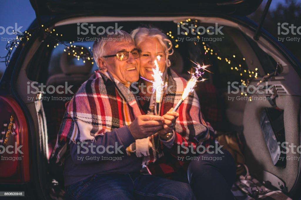 Älteres Paar im offenen Kofferraum sitzen und Funken Stöcke in den Händen zu halten – Foto