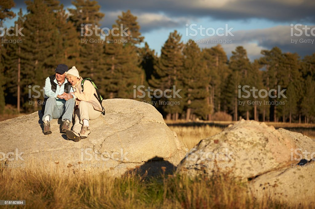 Senior couple sit on a rock near a forest, California, USA stock photo