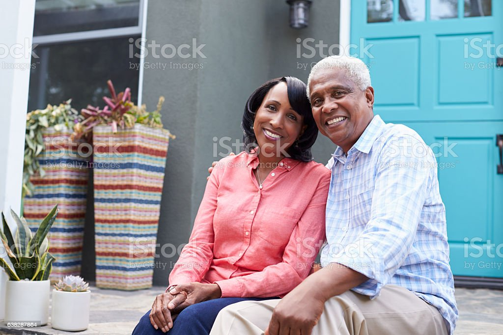 Senior couple sit on steps outside their house, close up stock photo