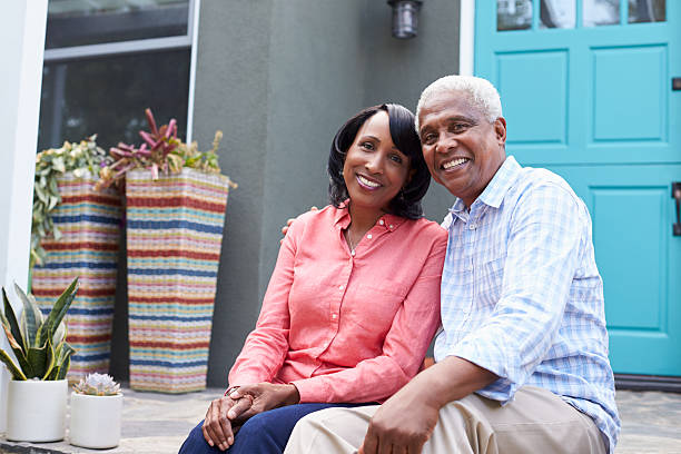 senior couple sit on steps outside their house, close up - senior housing stock photos and pictures