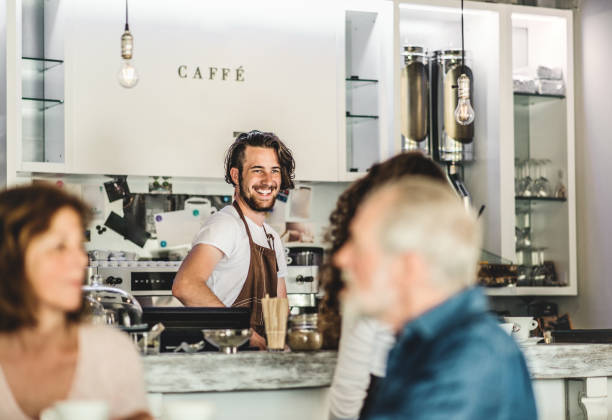 A senior couple sitting at the table and a young barista at the counter in a cafe. Unrecognizable senior couple sitting at the table and a young barista at the counter in a cafe. barista stock pictures, royalty-free photos & images