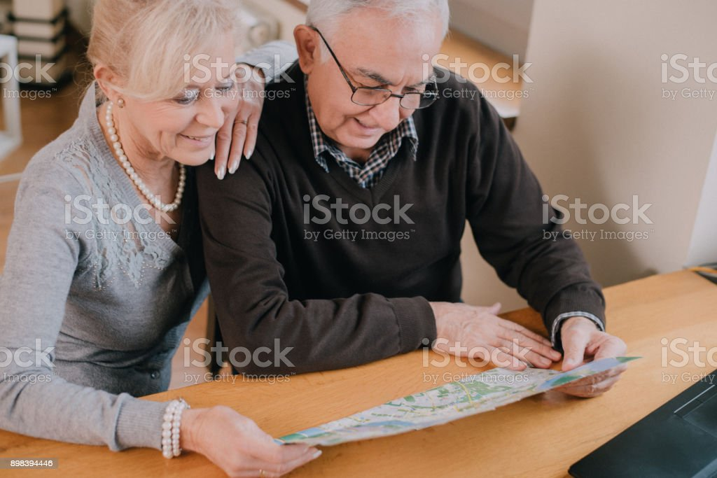 Senior couple sitting at the table in a living room and reading a map stock photo