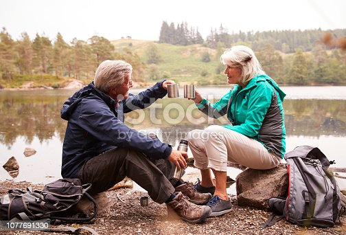 istock Senior couple sitting by a lake drinking coffee during camping holiday making a toast with their mugs, Lake District, UK 1077691330