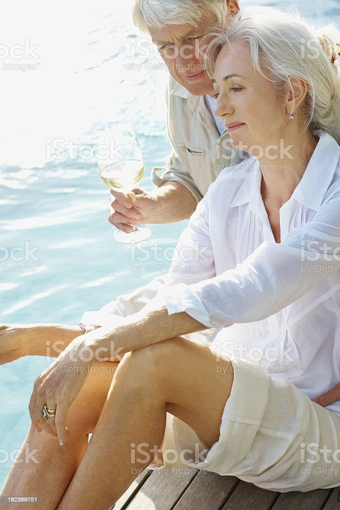 Senior couple sitting by the pool royalty-free stock photo