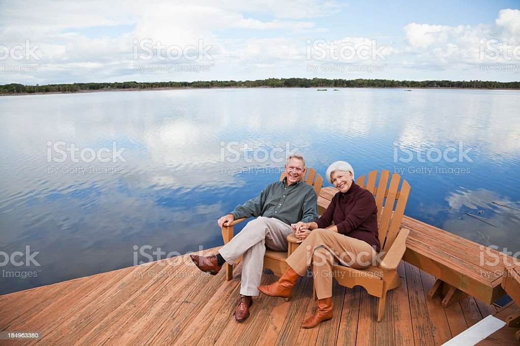Senior couple sitting by water stock photo