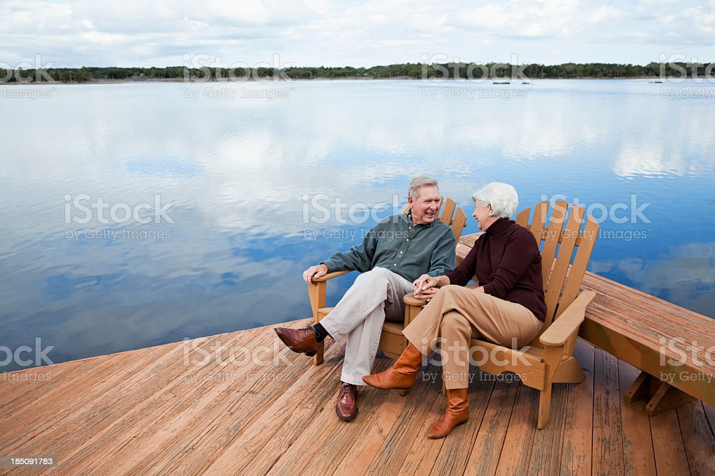 Senior couple sitting by water royalty-free stock photo