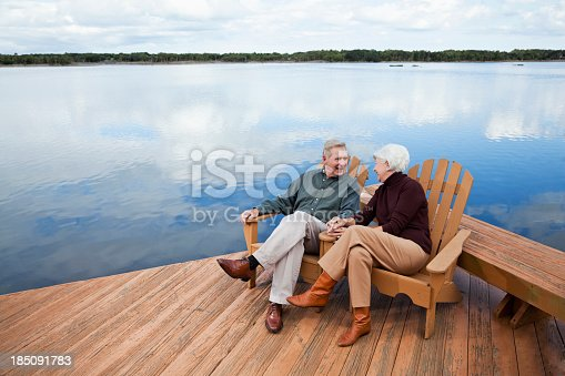 Senior couple (60s) sitting on wooden deck with water view.   Intracoastal Waterway, Florida.