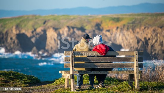 Smiling Caucasian Senior couple sitting in a bench after hiking  the mountain contemplating the ocean