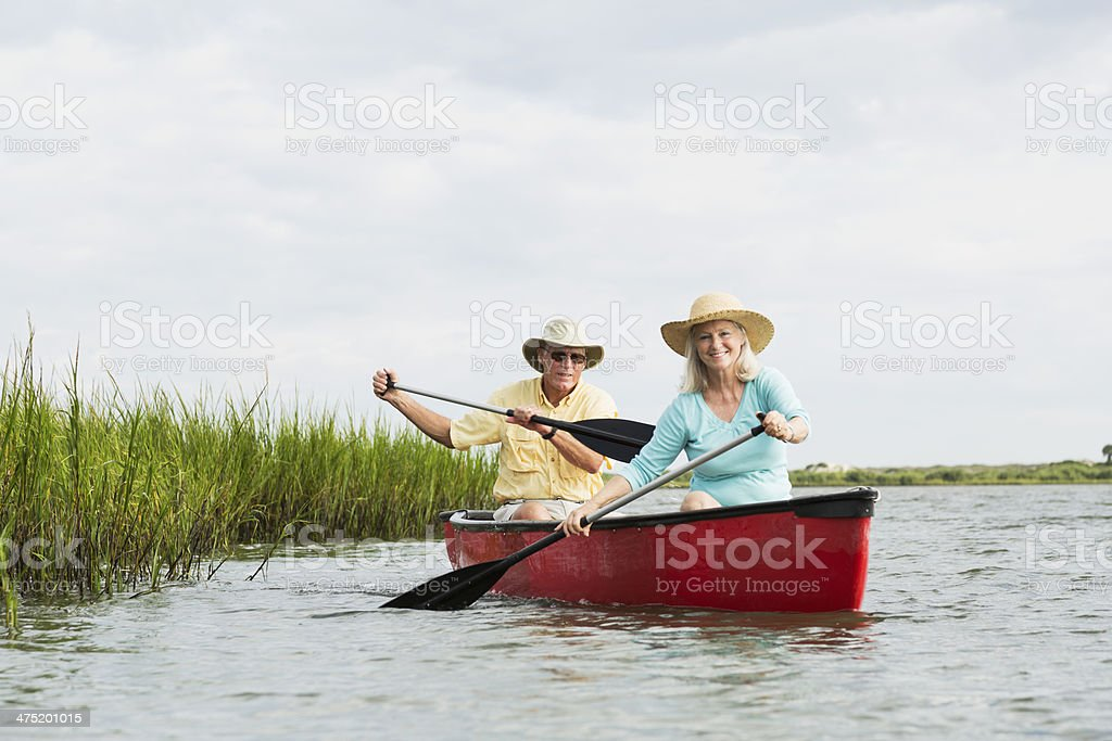 Senior couple sitting in canoe, paddling with oars stock photo