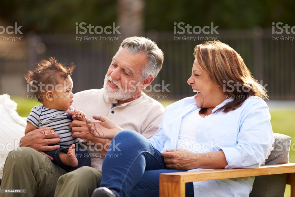Senior couple sitting in the garden with their baby grandson, smiling at him, front view royalty-free stock photo