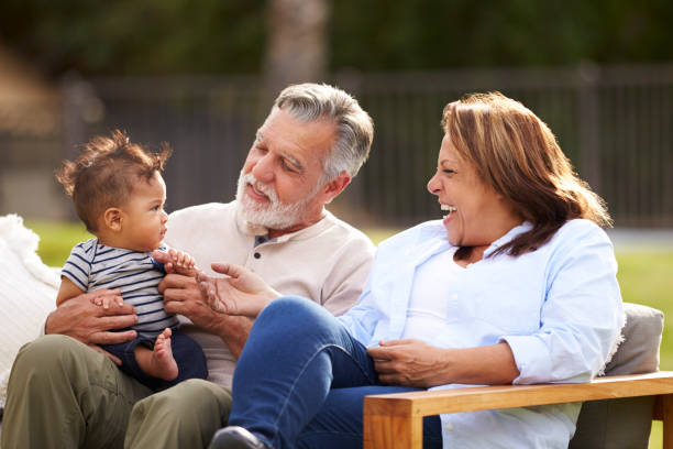 Senior couple sitting in the garden with their baby grandson, smiling at him, front view Senior couple sitting in the garden with their baby grandson, smiling at him, front view latin american and hispanic ethnicity stock pictures, royalty-free photos & images