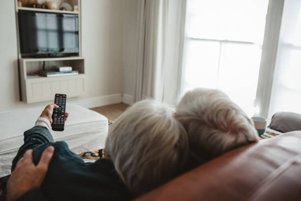 Senior couple sitting in their living room watching television stock photo