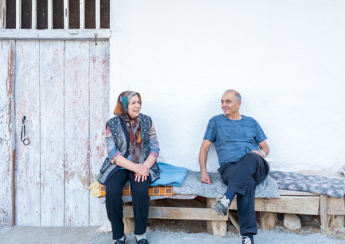 Senior Couple Sitting On A Bench In Front Of Village House