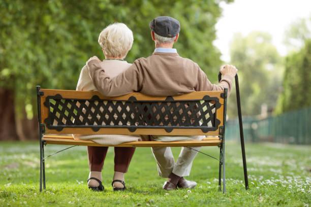 casal sênior sentado em um banco de madeira no parque - banco assento - fotografias e filmes do acervo