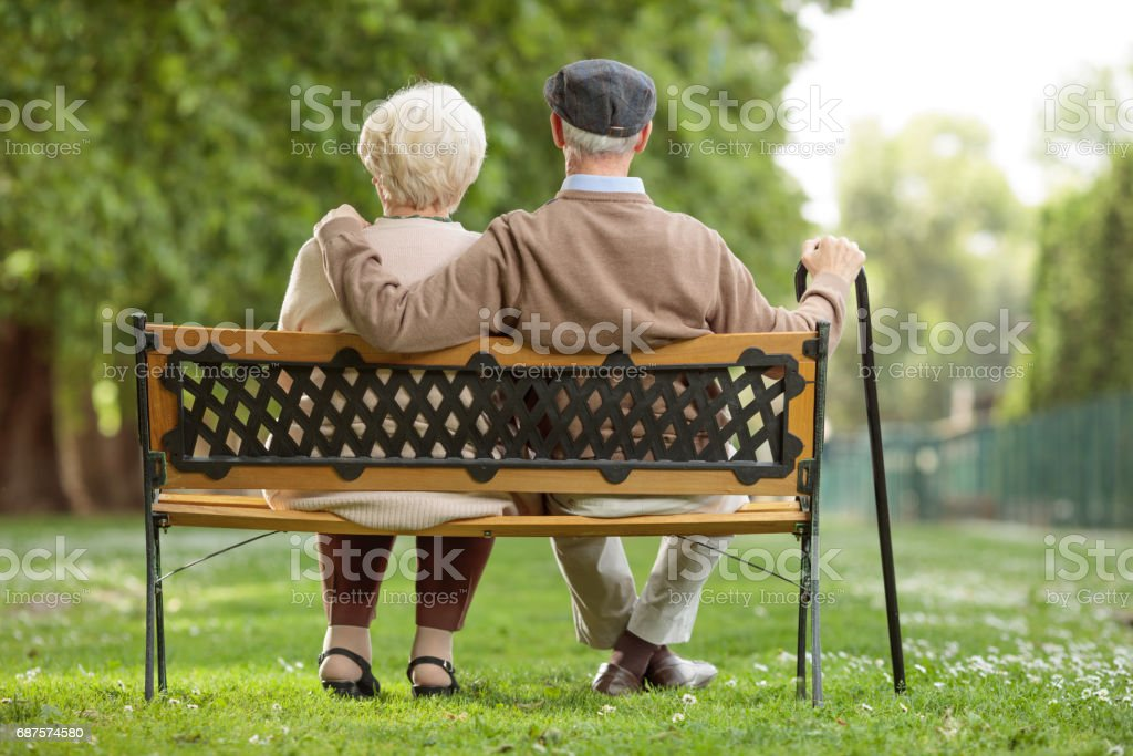 Senior couple sitting on a wooden bench in the park - foto de stock