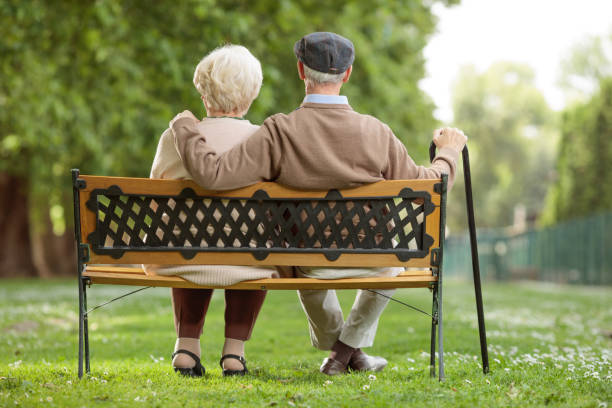 senior couple sitting on a wooden bench in the park - banc photos et images de collection