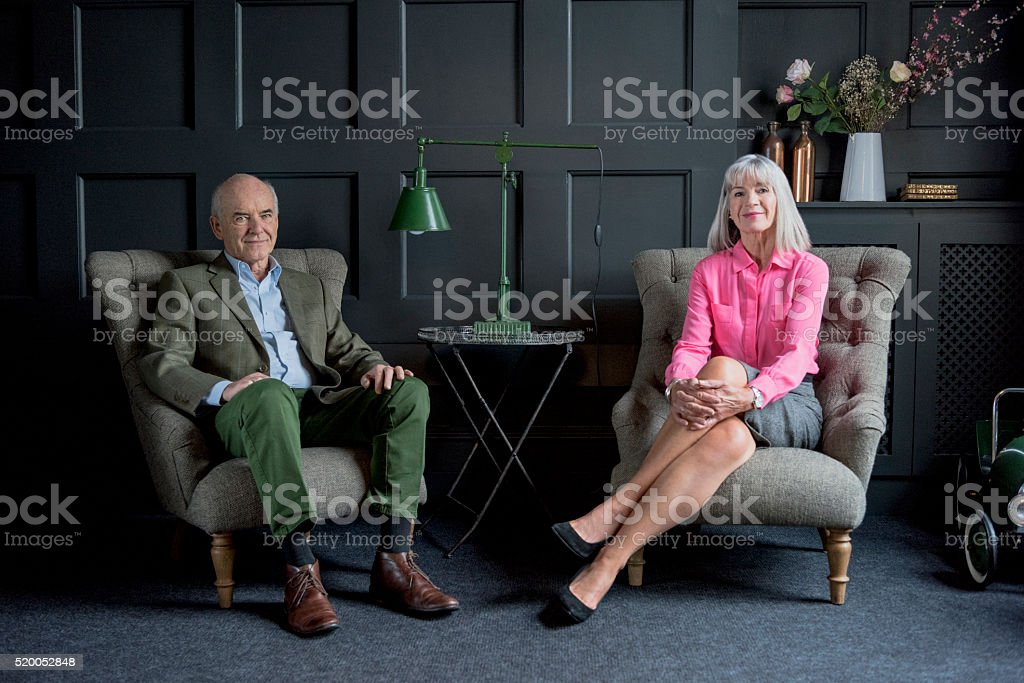 Senior couple sitting on armchairs in traditional living room stock photo