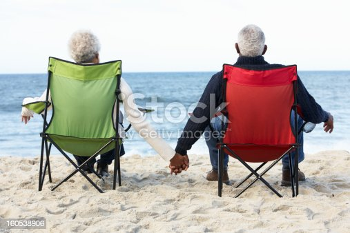 istock Senior Couple Sitting On Beach In Deck chairs 160538906