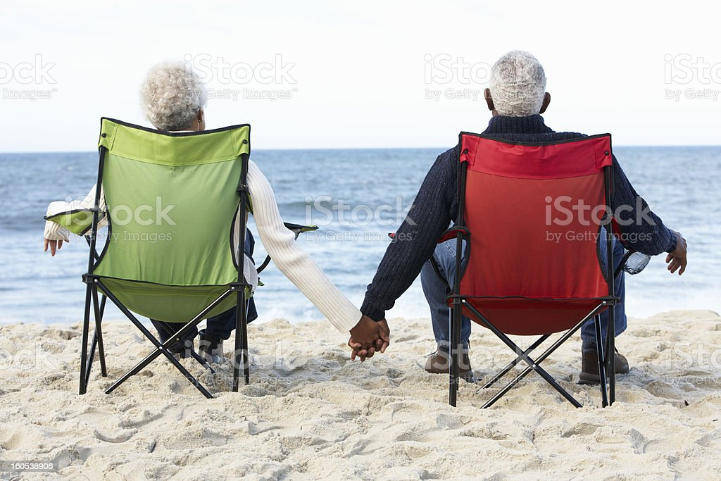 Senior Couple Sitting On Beach In Deck chairs stock photo