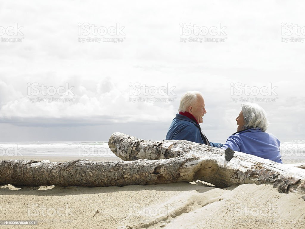 Senior couple sitting on beach royalty-free stock photo